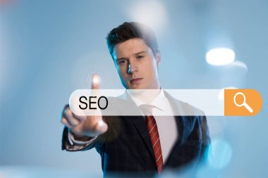 Confident businessman in suit pointing with finger at search bar with seo letters in front on blue background stock vector