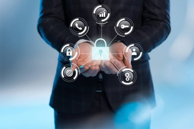 partial view of businessman with outstretched hands and internet security icons above on blue background