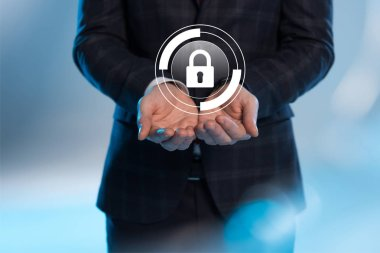 partial view of businessman with outstretched hands and internet security icon above on blue background