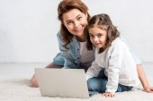 Smiling mother and daughter sitting on floor and using laptop on white