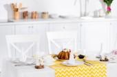 Velikonoční dort s malovanými vejci, keramický Zajíčci a nádobí na stole v kuchyni
