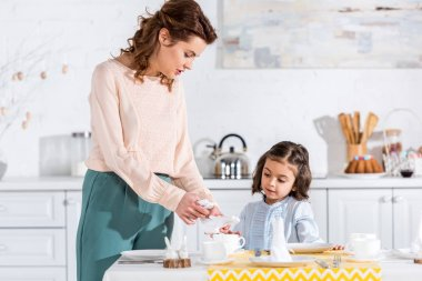 Mother and preschooler daughter decorating table with napkins in kitchen