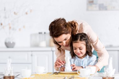 Mother and little daughter folding napkins at table in kitchen