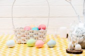 Fotografie Wicker basket with painted easter eggs and ceramic bunnies on table