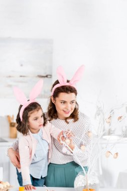 Happy mother and daughter in bunny ears decorating easter tree stock vector