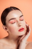 Fotografie beautiful stylish young woman touching face and posing with eyes closed isolated on coral