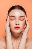 krásná moderní mladá žena s třpytky make-up a oči zavřené, dotýkání tváře izolované na korálových
