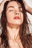 Fotografie schönes Mädchen mit Korallen Lippen, Hände am Kopf und nasses Haar posiert isoliert auf grau
