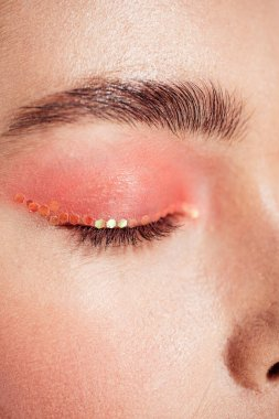 cropped view of woman with coral glitter makeup and eyes closed