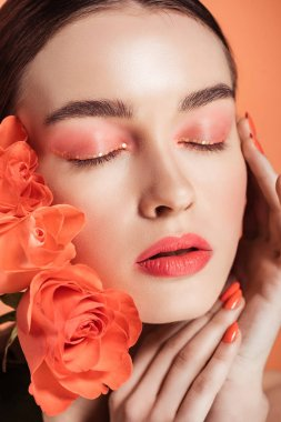 Beautiful stylish girl touching face and posing with rose flowers isolated on coral stock vector