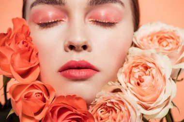 Beautiful trendy girl posing with rose flowers and eyes closed isolated on coral stock vector