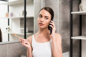 attractive brunette woman holding toothbrush while talking on smartphone in bathroom