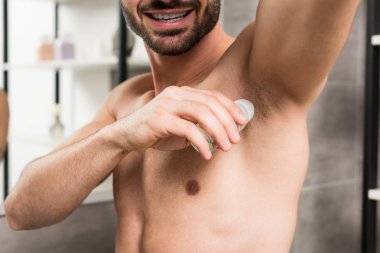 cropped view of happy shirtless man applying deodorant while standing in bathroom