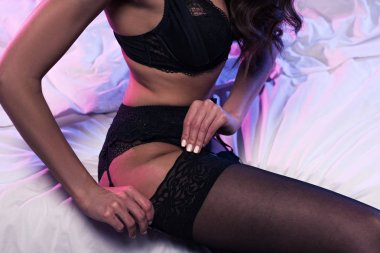 cropped view of sexy woman touching stocking while sitting on bed with neon light