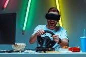 gutaussehender Mann mit Virtual-Reality-Headset und Lenkrad