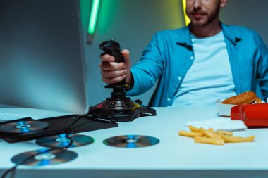 Selective focus of man playing video game with black joystick stock vector