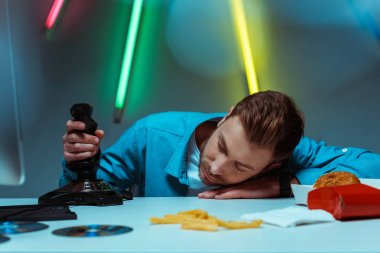 handsome young adult man sleeping on table and holding joystick