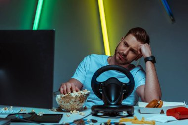 Handsome and sad man looking at computer monitor and eating popcorn stock vector