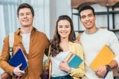 Tři šťastní multietničtí studenti, kteří drží zápisníky a knihy a dívají se na kameru