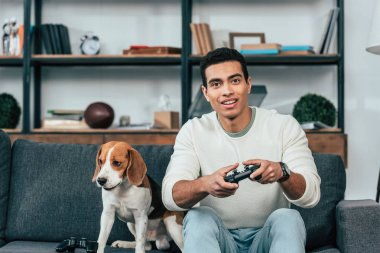 Young man with dog sitting on sofa and holding joystick stock vector