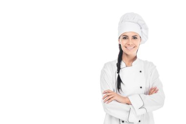 Smiling chef in hat standing with crossed arms isolated on white