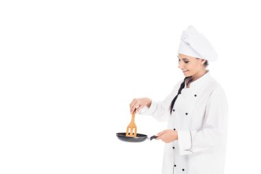 Chef in hat holding frying pan and wooden kitchen spatula isolated on white