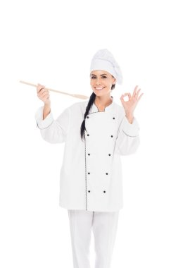 Smiling chef in uniform holding wooden spatula and showing okay sign isolated on white stock vector