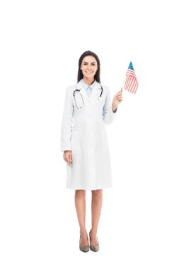 Full length view of smiling doctor with stethoscope holding american flag isolated on white