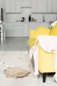 Photo carpet and bright yellow sofa with cloths and papers