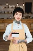 Lächelnde Kellnerin in Schürze mit Kreditkarte und Blick in die Kamera