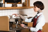 pretty tattooed barista preparing coffee on coffee machine