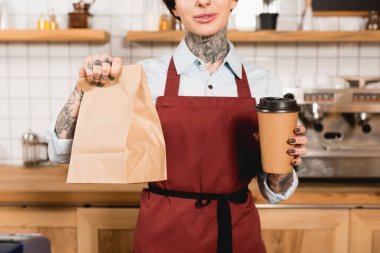 Partial view of barista in apron holding paper bag and disposable cup stock vector