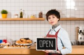 Fotografie attractive barista holding signboard with open lettering and looking at camera