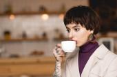 fehér kávé csésze kávét iszik, töprengő, divatos üzletasszony