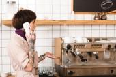 beszélő smartphone állva eszpresszó gép közelében meglepett üzletasszony