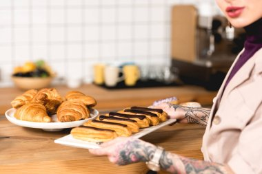 cropped view of cafe owner placing dish with eclairs on bar counter in coffee shop