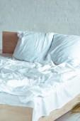 dřevěné a útulnou postel s polštáře, deky, list v ložnici