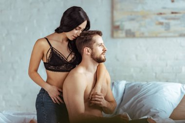 attractive woman in bra and handsome, muscular and shirtless man hugging in bedroom