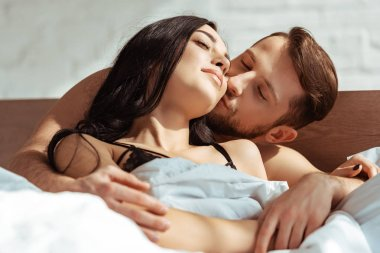 good-looking man kissing beautiful and brunette woman in bedroom