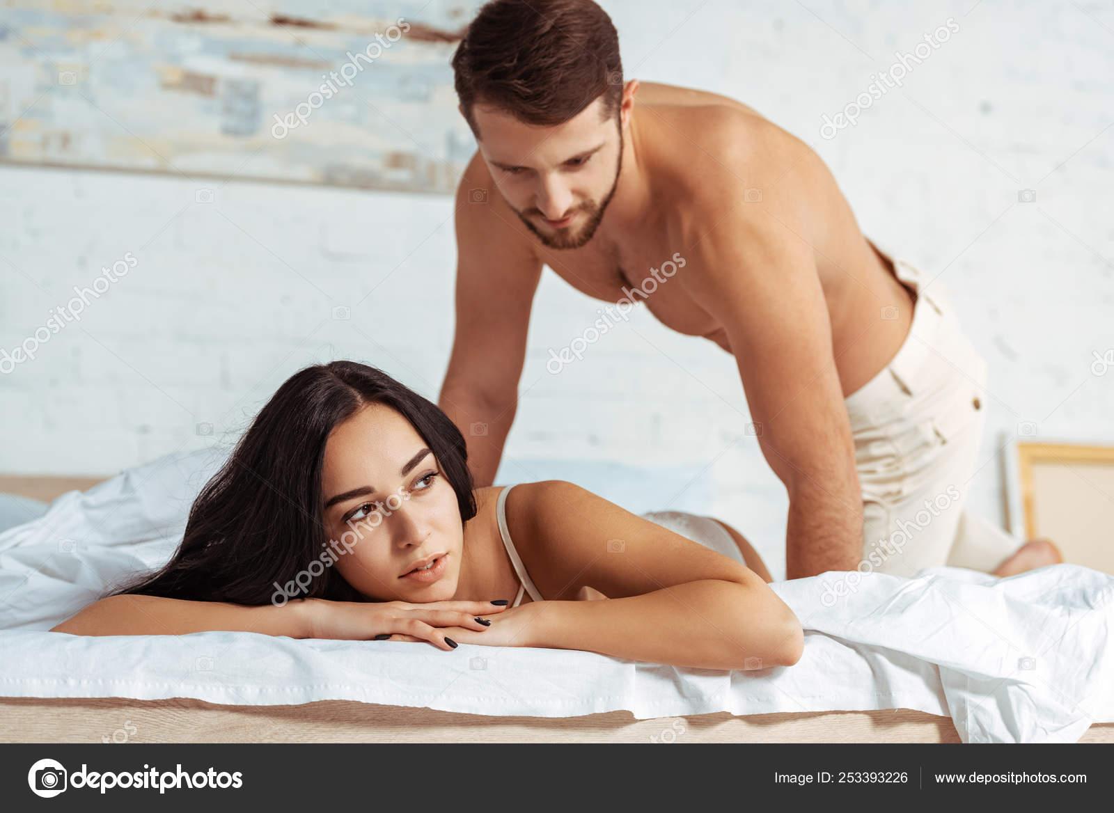 beautiful woman lying bed shirtless man looking her bedroom stock photo c igorvetushko 253393226