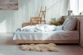 interiér ložnice s útulnou postel, polštáře, přikrývky, obrázky a stojan
