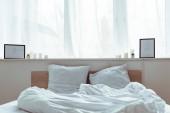 moderní ložnice s útulnou postel, polštáře, deky, obrázky v denní