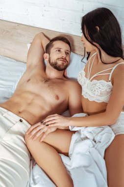 handsome and muscular man lying in bed and hugging with beautiful woman in lace bra in bedroom