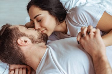handsome man and beautiful woman lying in bed and kissing in bedroom