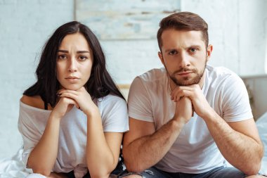 handsome man in jeans and beautiful sad woman in t-shirt sitting on bed and looking at camera