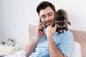 Photo smiling handsome man talking on smartphone while funny raccoon sitting on his shoulder