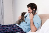 Fotografie happy handsome man talking on smartphone while cuddling with adorable raccoon in bedroom