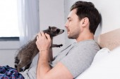 Photo handsome man cuddling with funny raccoon in bedroom at home
