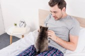Fotografie funny raccoon sitting with handsome man on bed in bedroom