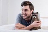 Fotografie cheerful man cuddling with adorable raccoon on bed at home
